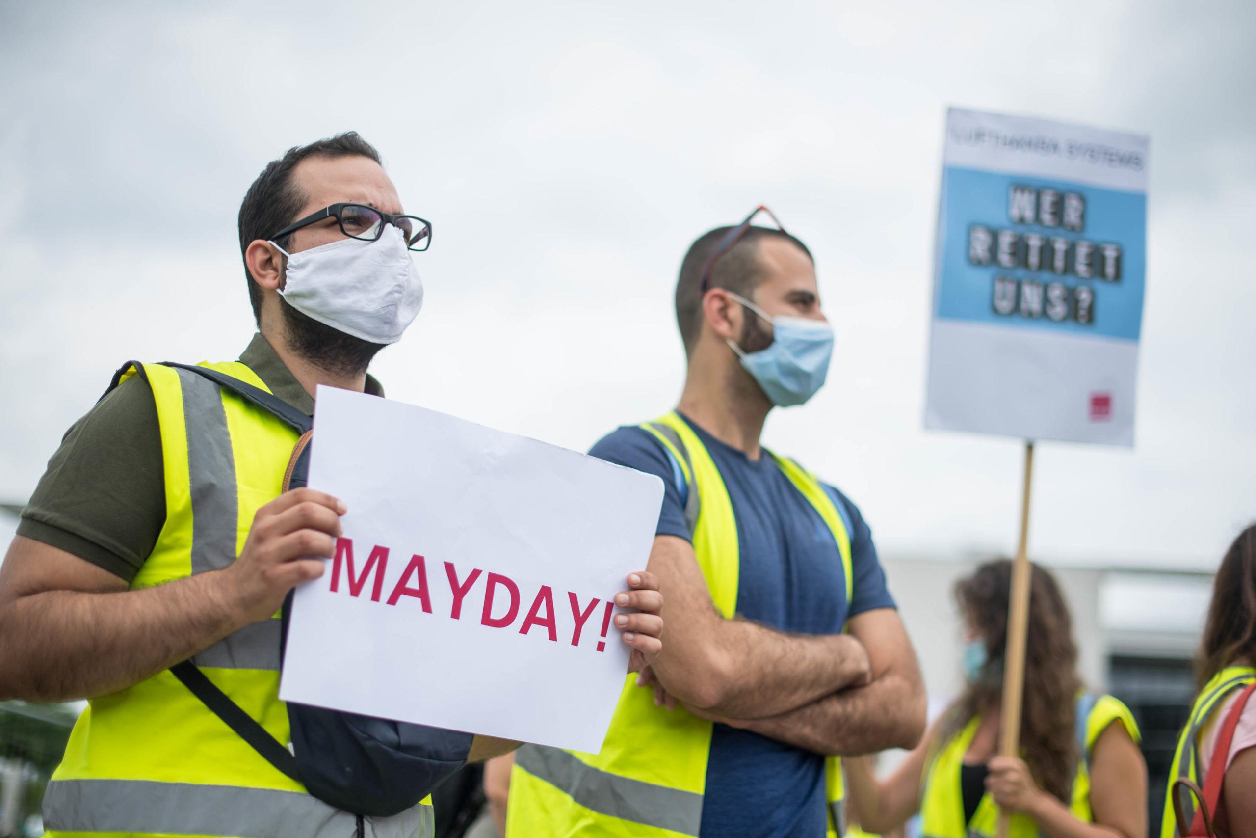"""Demonstrant mit Plakat Aufschrift """"Mayday"""""""